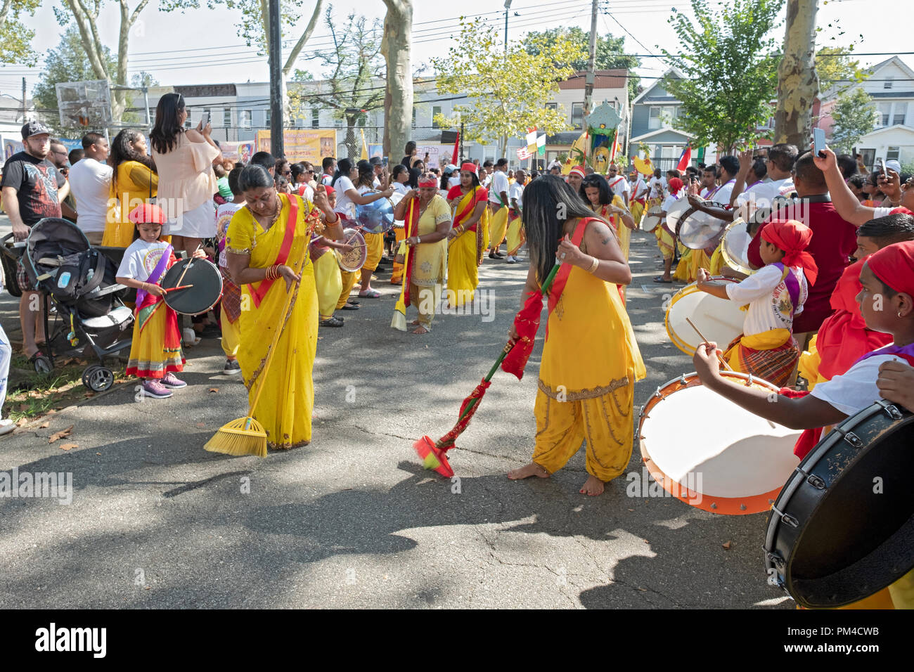 Devout Hindu women sweep a path where statues of deities will parade. In Smokey Park in South Richmond Hill, Queens, New York. - Stock Image