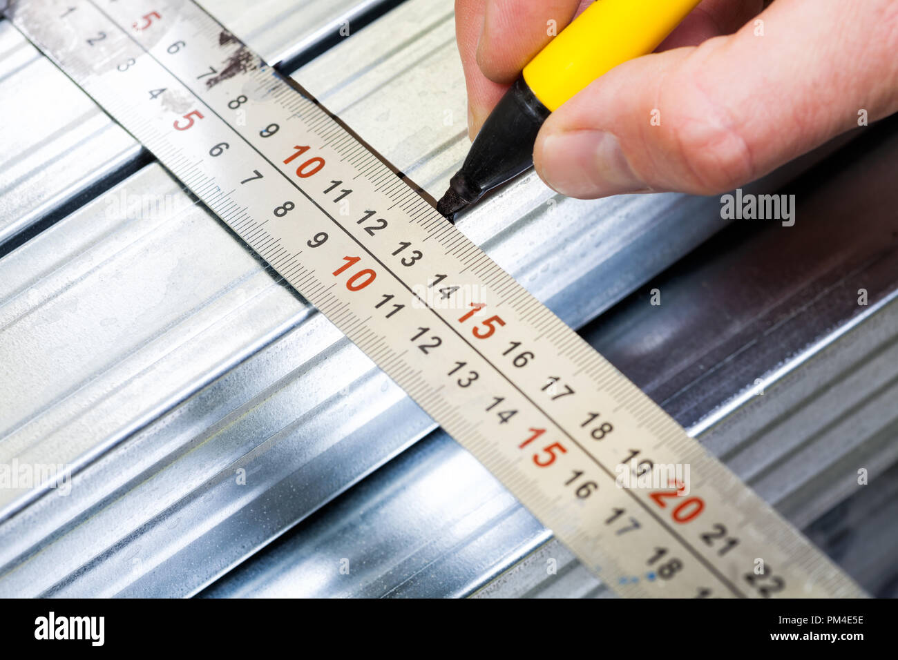 Person marking a  measurement on a metal stud with marker pen while constructing plasterboard frame - Stock Image