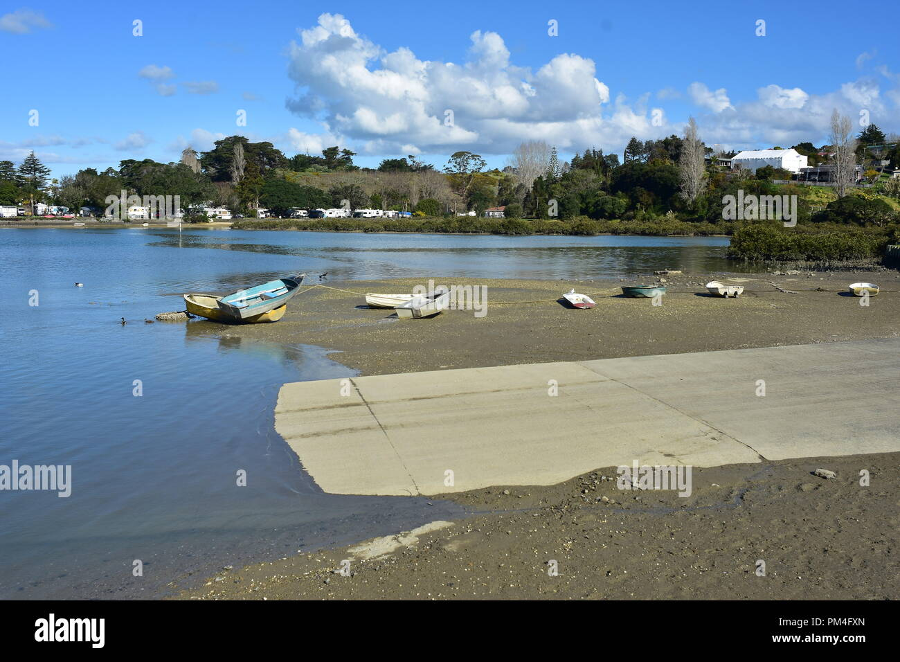 Small dinghies on mud flats next to concrete boat ramp in estuary at low tide. Stock Photo