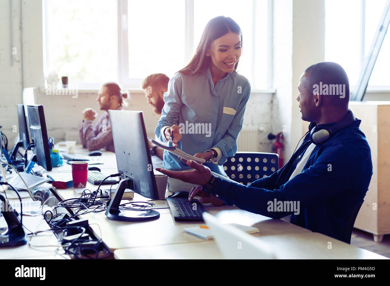Busy working day. Top view of young modern people in smart casual wear discussing business while sitting in the creative office. - Stock Image