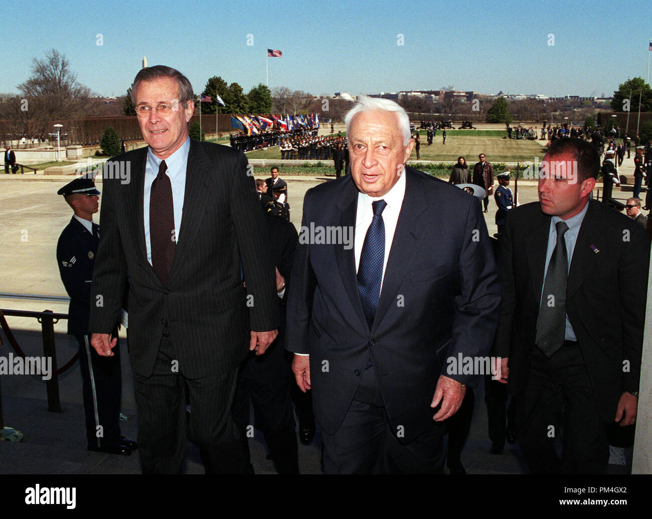 Secretary of Defense Donald H. Rumsfeld (left), escorts Israeli Prime Minister Ariel Sharon (center) into the Pentagon at the conclusion of a full honor arrival ceremony for Sharon at the Pentagon on March 19, 2001.  Rumsfeld and Sharon will meet to discuss regional and international security issues of interest to both nations.  DoD photo by R. D. Ward.  (Released)   File Reference # 1003_127THA - Stock Image