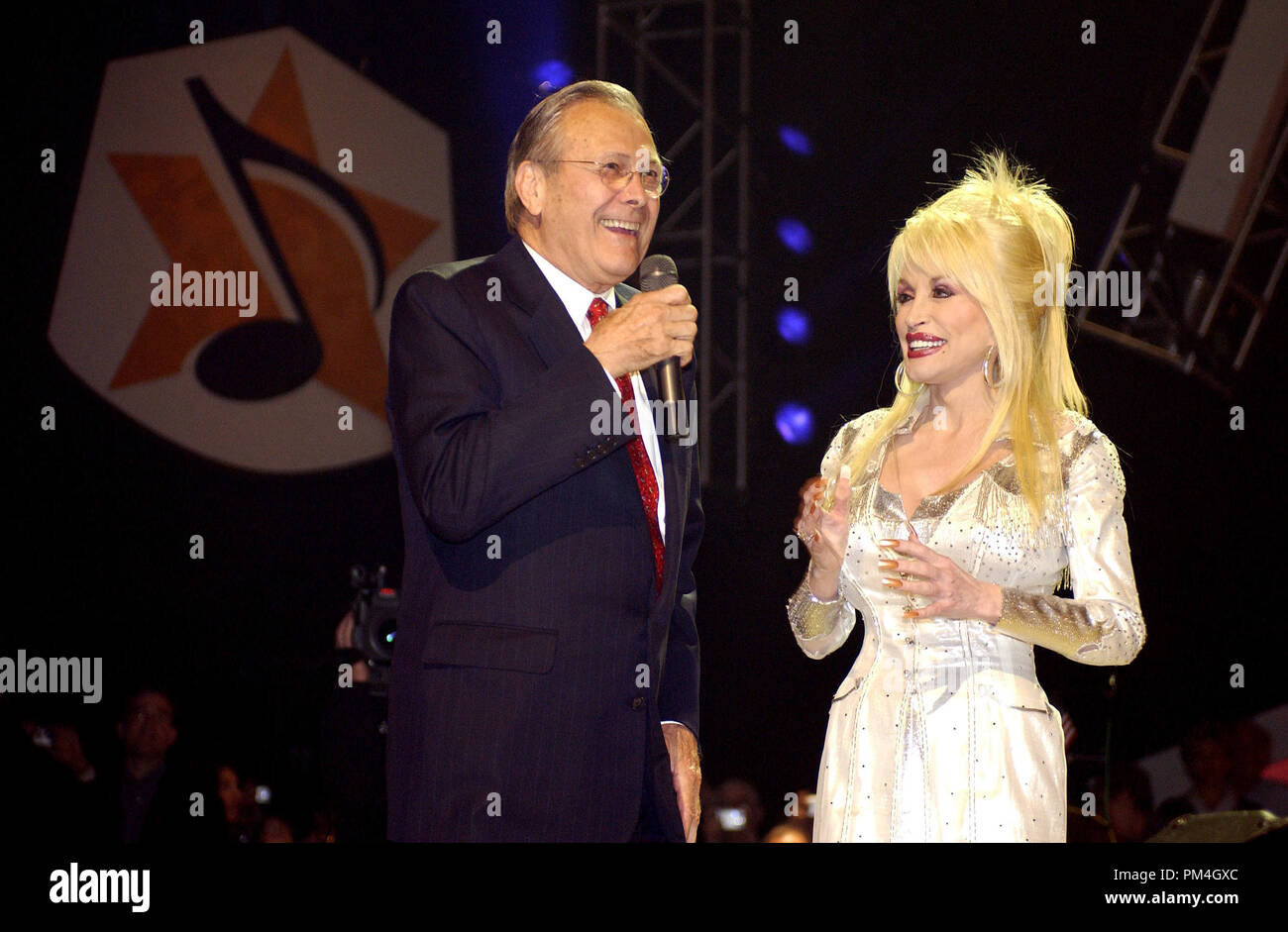 Secretary of Defense Donald H. Rumsfeld joins country music legend Dolly Parton on stage at the Grand Ole Opry during a live broadcast in Nashville, Tenn., on April 23, 2005.  Rumsfeld visited Nashville to thank Parton, the Grand Ole Opry, and the American people for their support of U.S. troops.  DoD photo by Tech. Sgt. Cherie A. Thurlby, U.S. Air Force. (Released)     File Reference # 1003_132THA - Stock Image