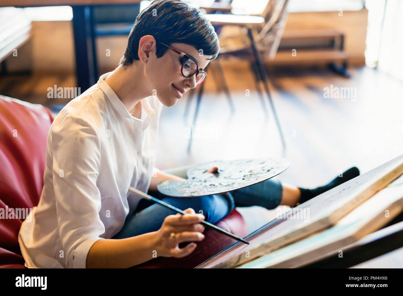Female artist painting with palette and paintbrush - Stock Image