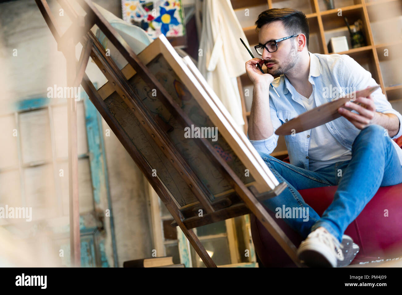 Portrait Of Male Artist Working On Painting In Studio - Stock Image