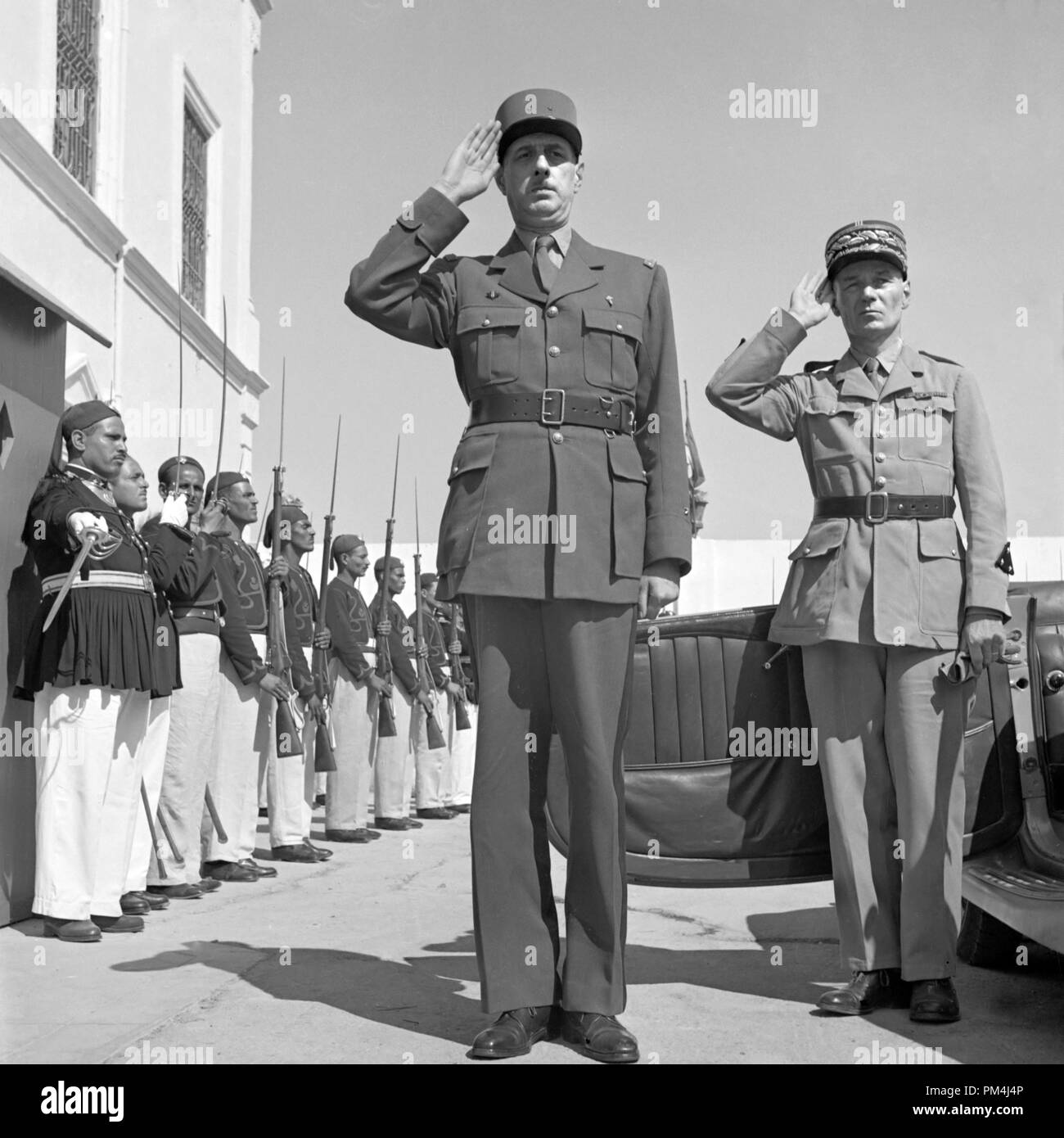 General de Gaulle, accompanied by General Mast, saluting as the band plays Marseillaise outside the summer palace of the bay of Tunis. June 1943   File Reference # 1003_521THA - Stock Image