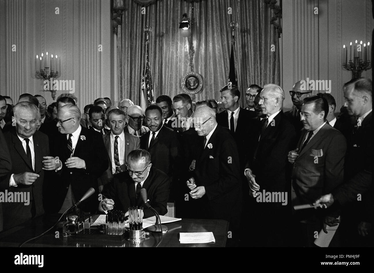 U.S. President Lyndon Baines Johnson Signs the Civil Rights Act of 1964 while Martin Luther King and others witness the signing. Photo by Cecil Stoughton, White House Press Office   File Reference # 1003 621THA Stock Photo
