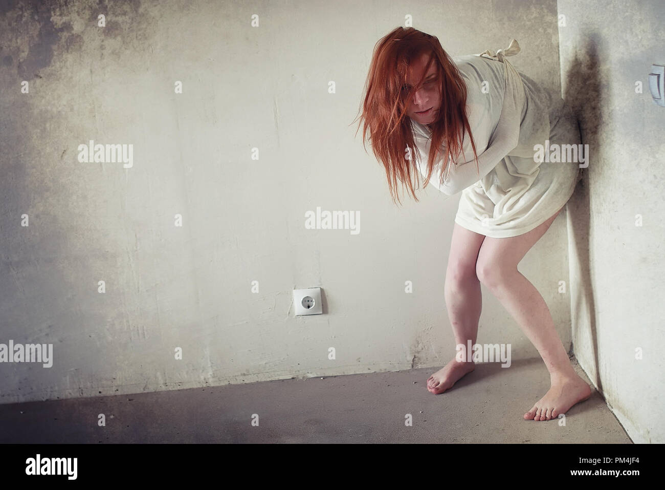 A girl with red hair in a shirt. Domestic violence and sacrifice. Girl with a sick psyche. - Stock Image