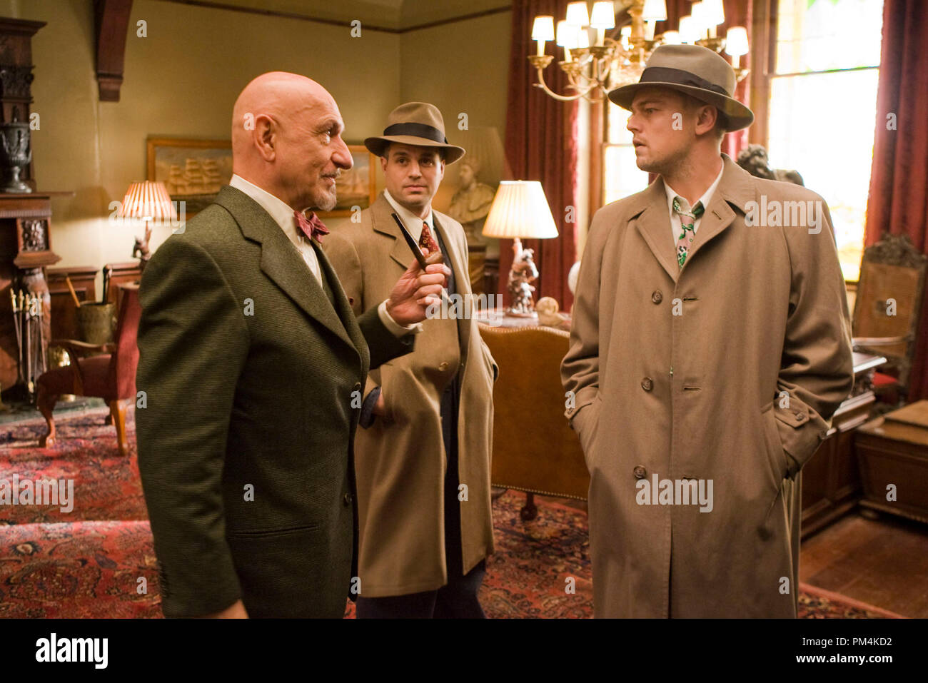 """(Left to right) Dr. Cawley (Ben Kingsley) hears Chuck Aule (Mark Ruffalo) and Teddy Daniels' (Leonardo DiCaprio) suspicions about the mysterious disappearance on an island prison for the criminally insane in the thriller """"Shutter Island."""" - Stock Image"""