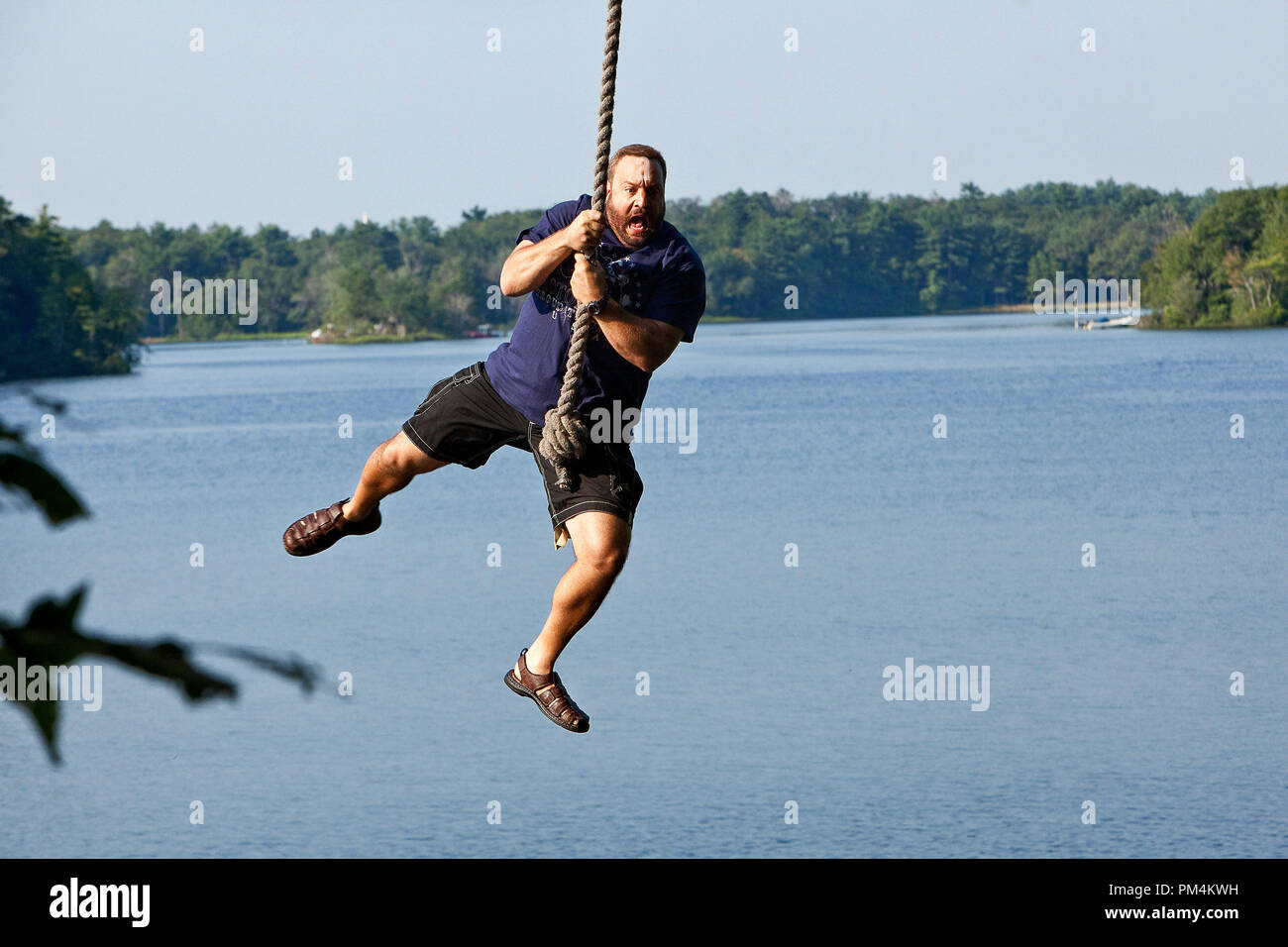 Eric Lamonsoff (Kevin James) shows the kids what they used to do when they were younger on the rope swing in Columbia Pictures' GROWN UPS. - Stock Image