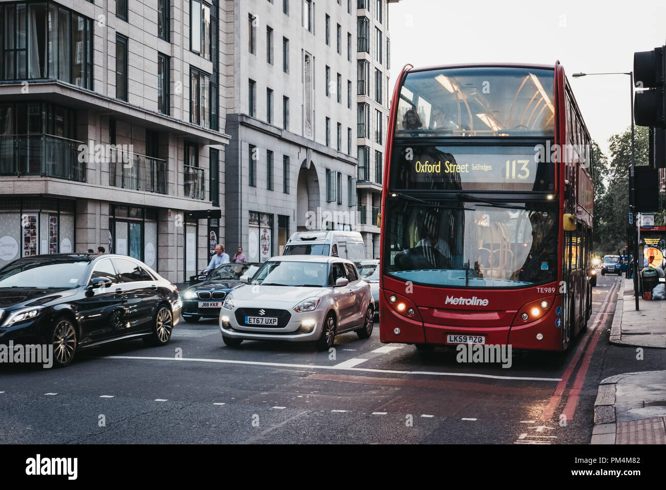 London, UK - July 26, 2018: Cars and a red double decker bus number 113 towards Oxford Street on a street in Marylebone, London, UK, at dusk. Double d Stock Photo