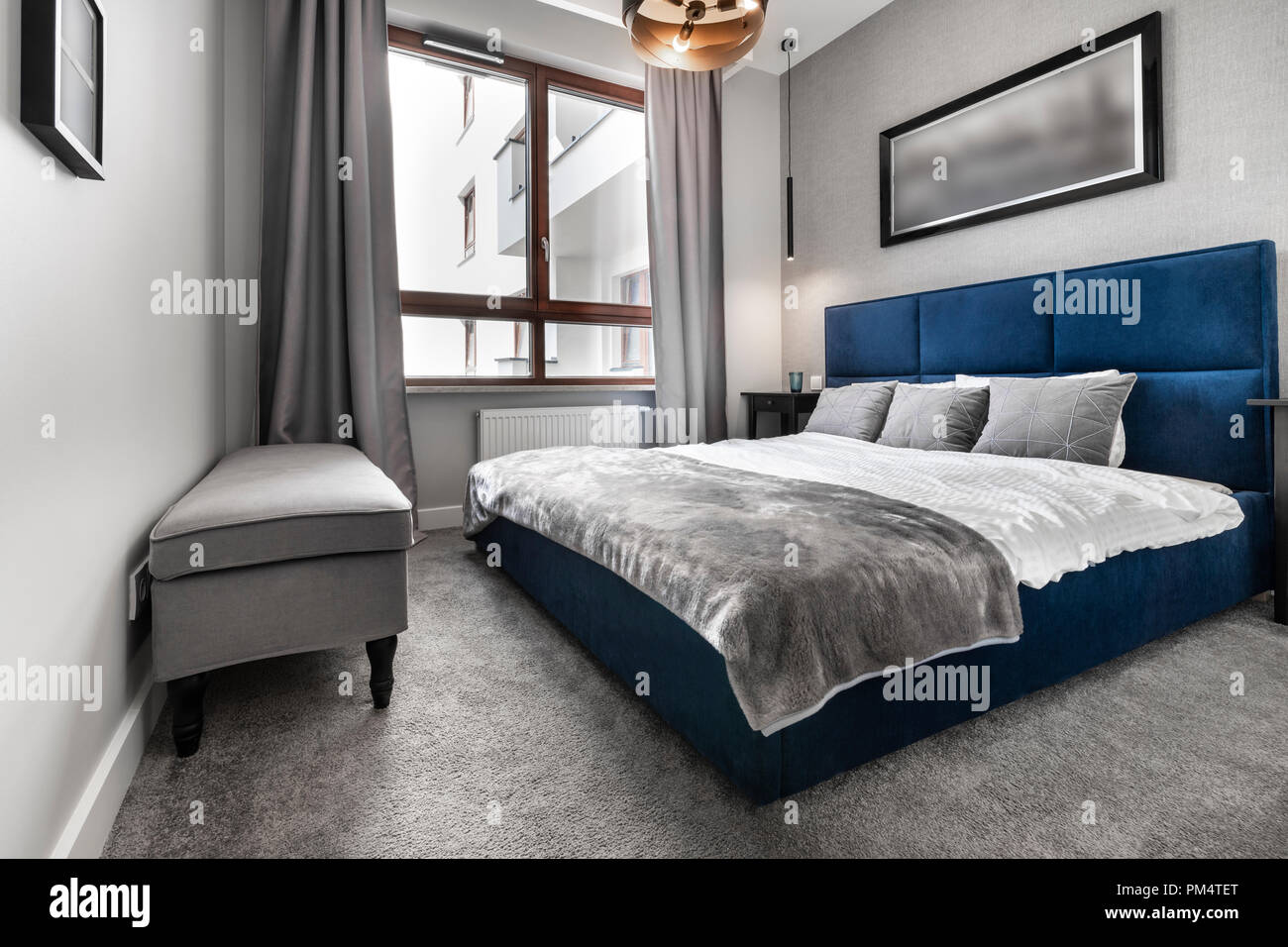 Modern bedroom in gray finishing with blue bed Stock Photo ...