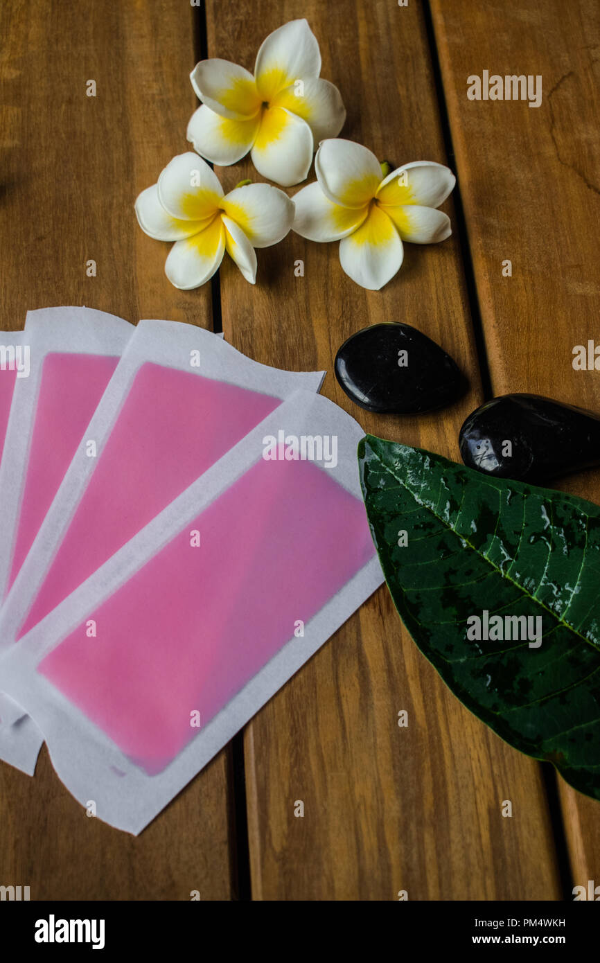 Pink cold wax strips on wooden surface with plumeria flowers and black round stones - Stock Image