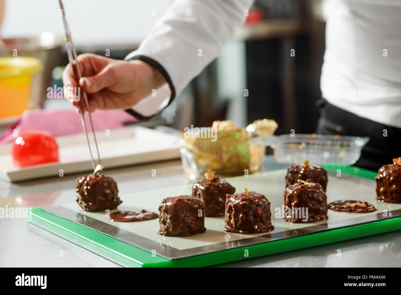 Placing decorations with kitchen tongs - Stock Image