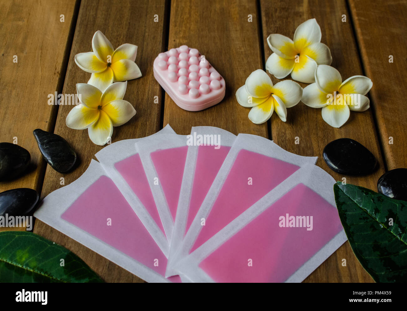 Pink cold wax strips and pink soap bar on wooden surface with plumeria flowers and black round stones - Stock Image
