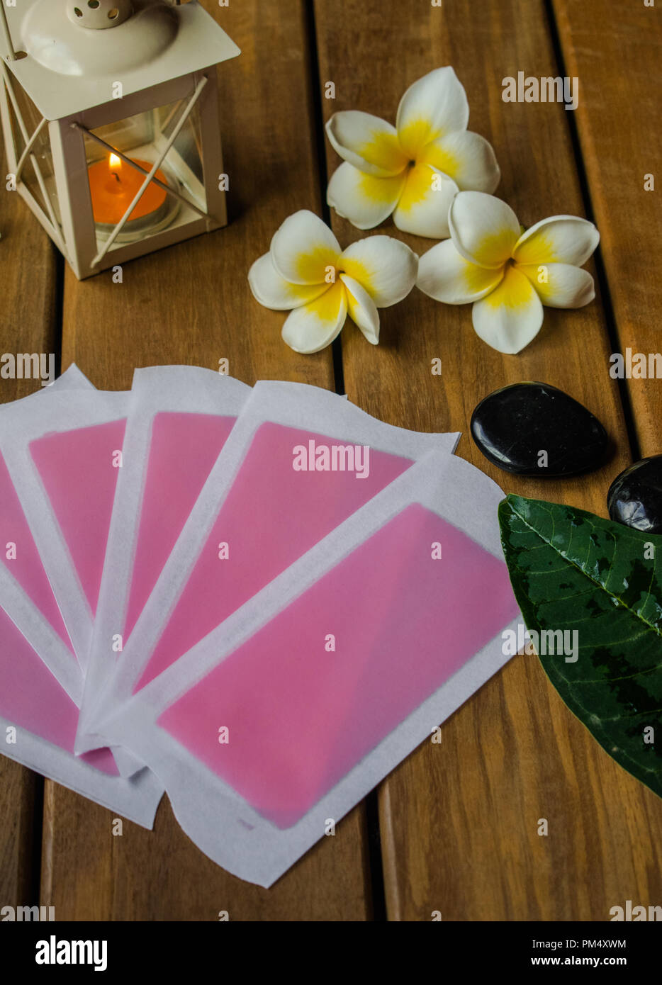 Pink cold waz strips on wooden surface with plumeria flowers, black round stones and orange candle - Stock Image