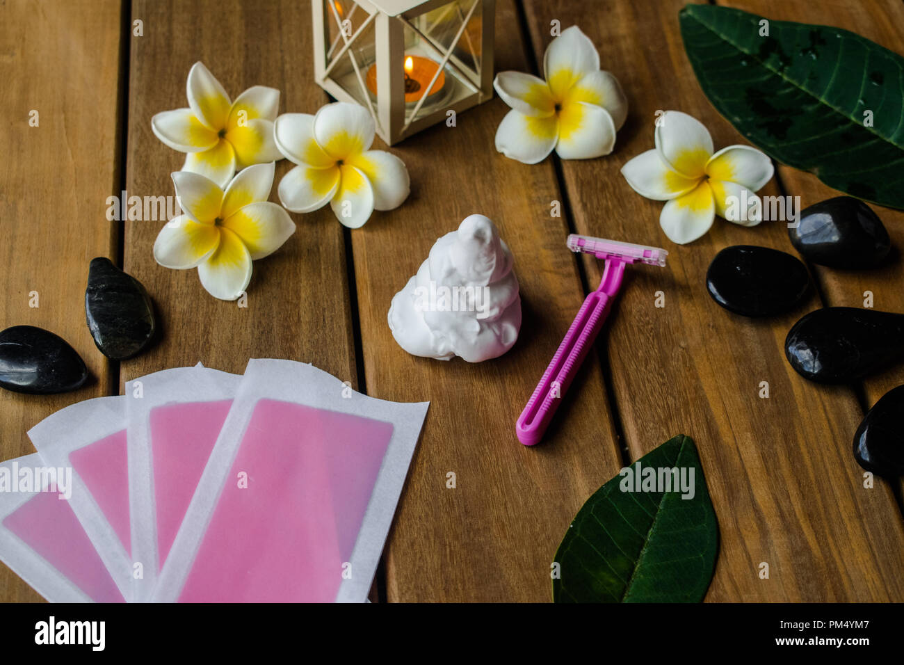 Pink cold wax strips with pink razor blade on wooden surface with plumeria flowers and black round stones - Stock Image