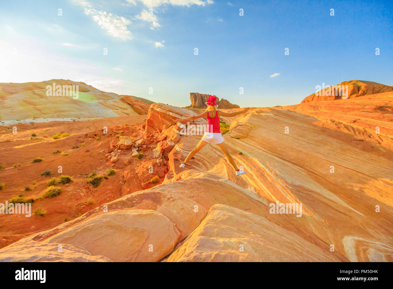 Young tourist girl jumping over Fire Wave in Valley of Fire, Nevada, USA, at red sunset. Happy hiker enjoying view of popular striped lines around the lip of Fire Wave. Gibraltar rock on background. Stock Photo
