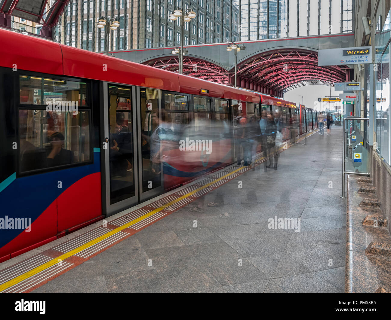 DOCKLANDS, LONDON:  DLR Train in Canary Wharf Station with People shown with Motion Blur - Stock Image