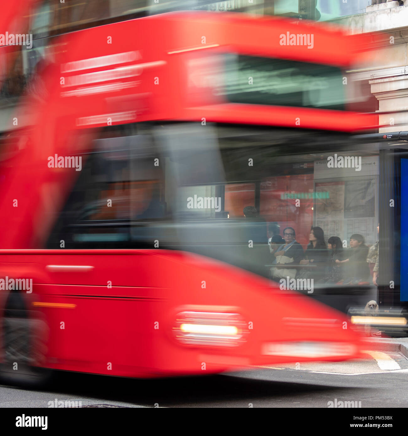 LONDON:  Red Double Decker Bus with motion blur passing people at Bust Stop in the West End - Stock Image