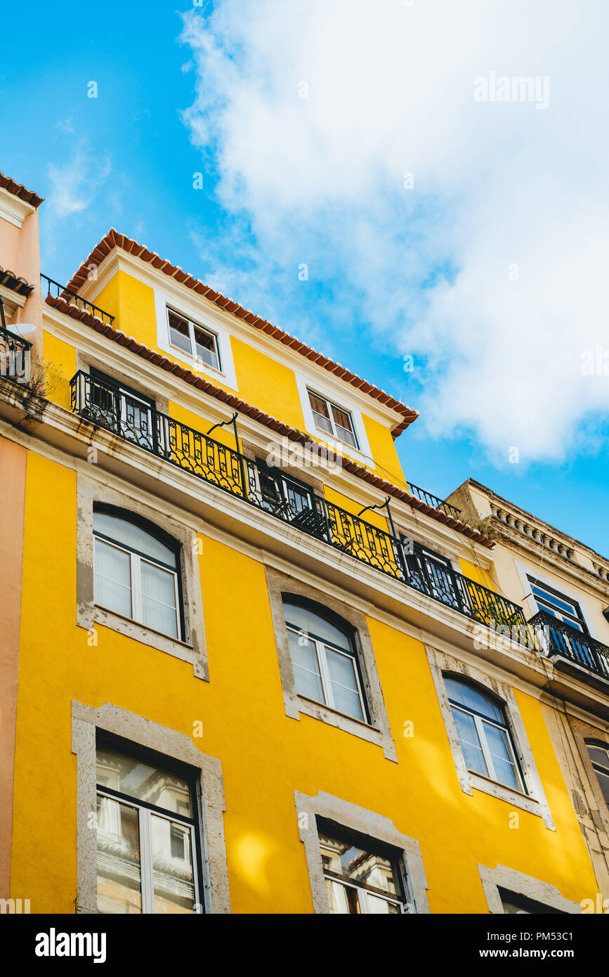 Portuguese architecture of a yellow multi-story building with windows and balconies and a red tile roof; blue sky with clouds. - Stock Image