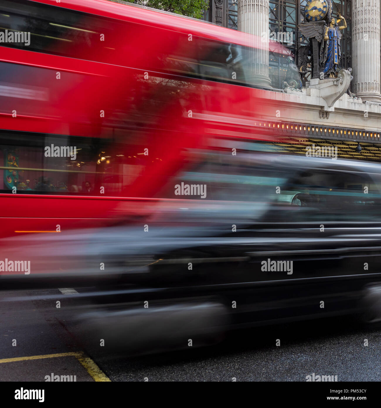 LONDON:  Black Taxi cab passing a Red Double Decker Bus with motion blur in the West End - Stock Image