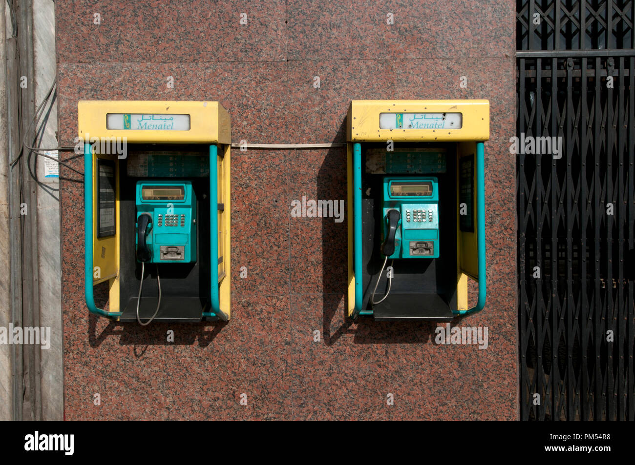 Egypt, Cairo 2014. Two yellow and turquoise phone boxes. - Stock Image