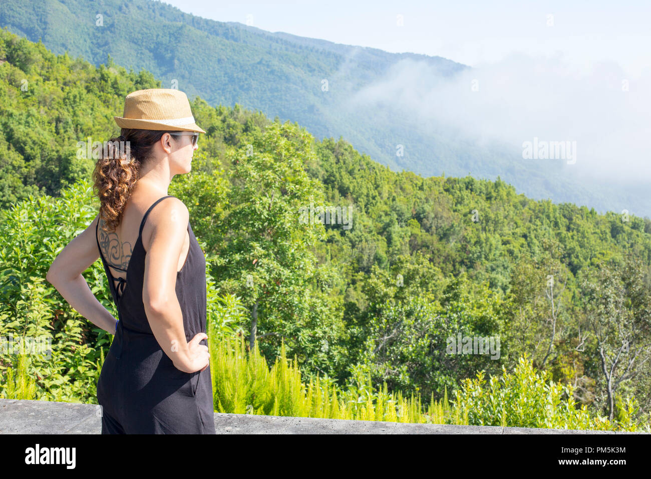 woman with hat and tattoo looking from atop a mountain.jpgwoman with woman with hat and tattoo looking from atop a mountain.jpg - Stock Image