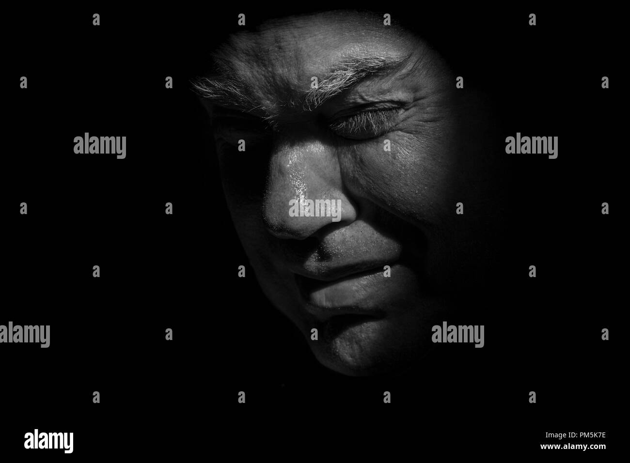 Model released closeup of man's face, looking desperate, distressed, in anguish & despair while squinting in bright moody lights. Concept. - Stock Image