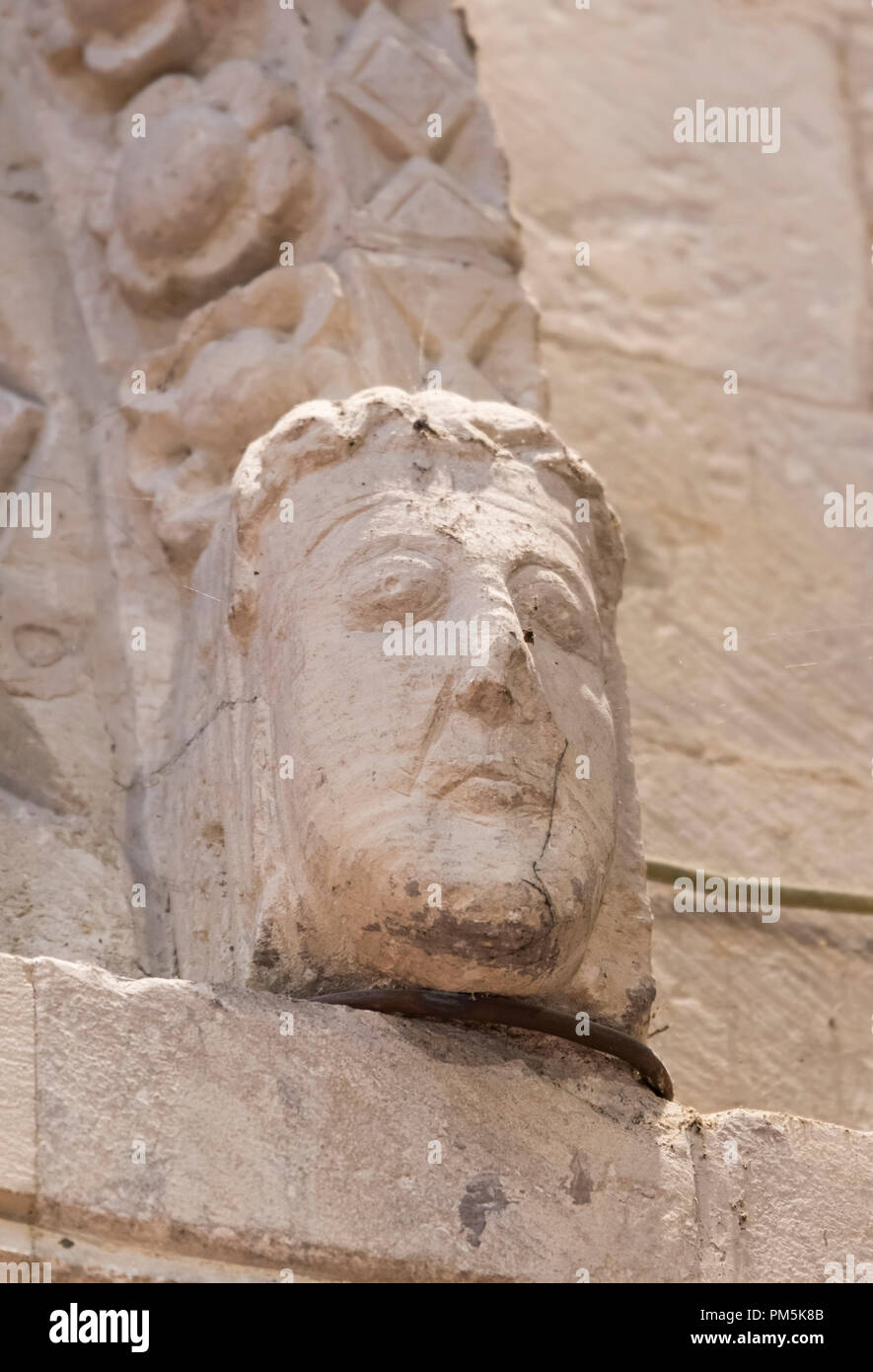 Man's head carved from a stone arch at the historic Norman St Nicolas Church in Old Shoreham, West Sussex, England, UK. Grade 1 listed building. - Stock Image