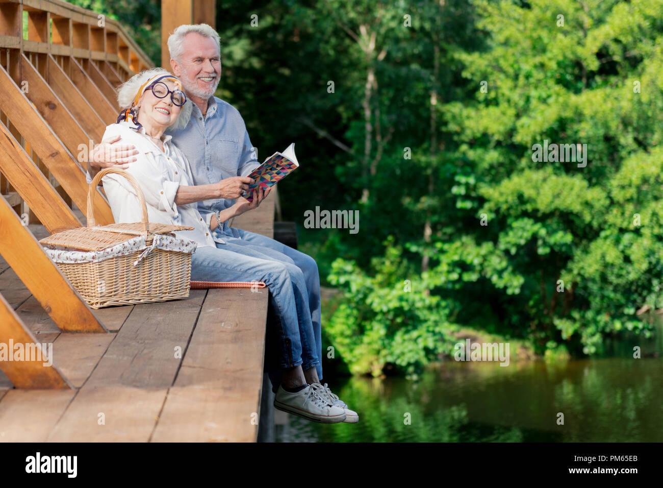 Beautiful aged couple sitting on the bridge and hugging - Stock Image