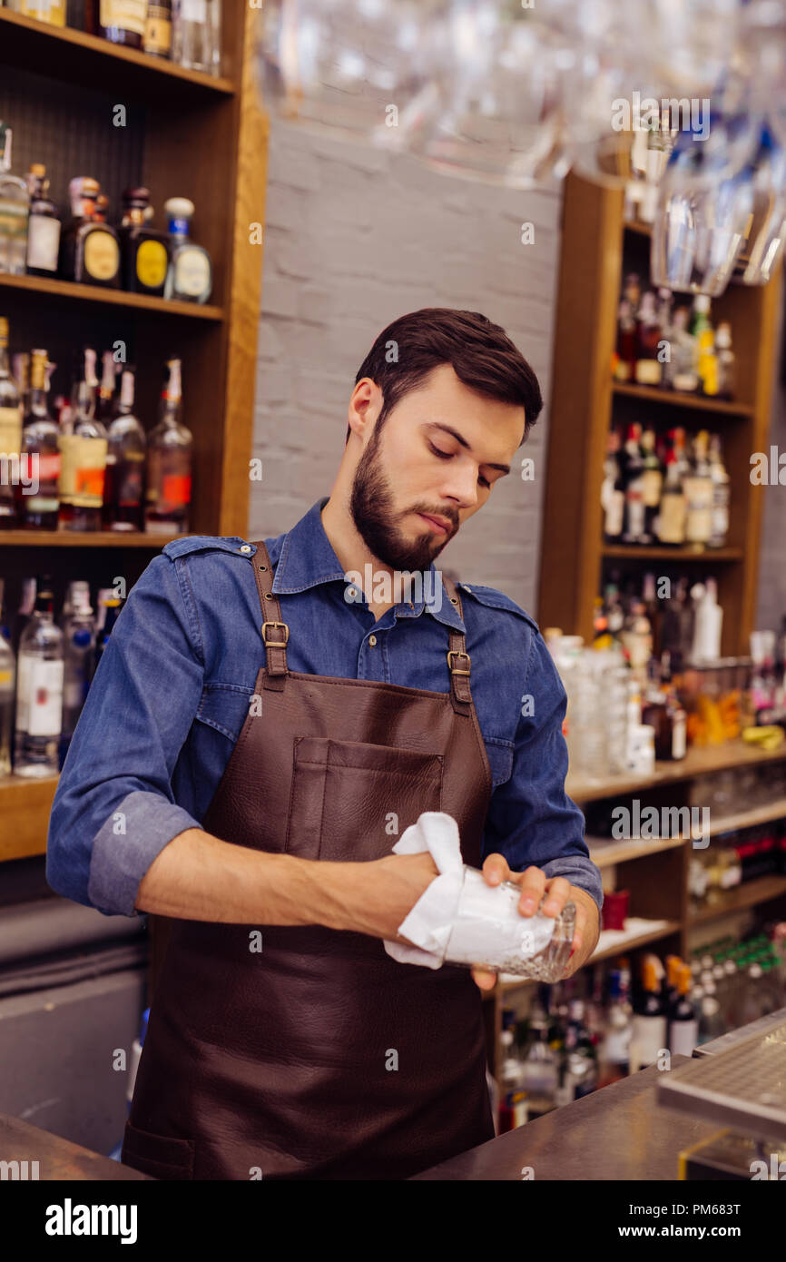 Professional barman looking serious while cleaning the glasses - Stock Image