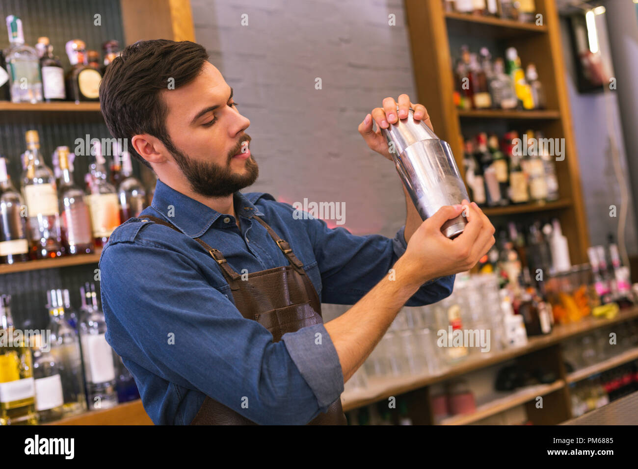 Careful barman looking concentrated while making cocktails - Stock Image