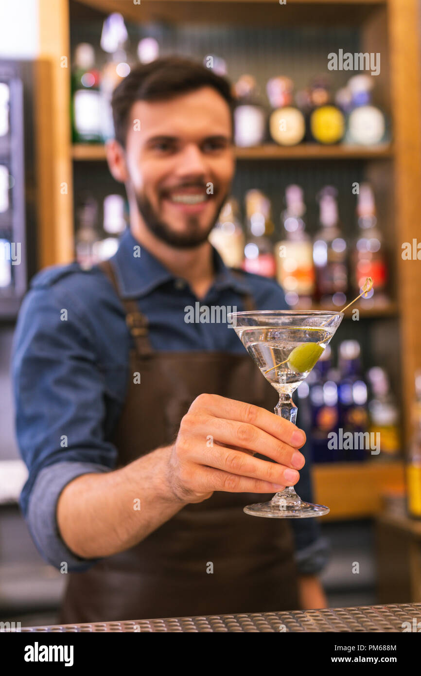 Positive barman smiling while offering cold alcohol drink - Stock Image