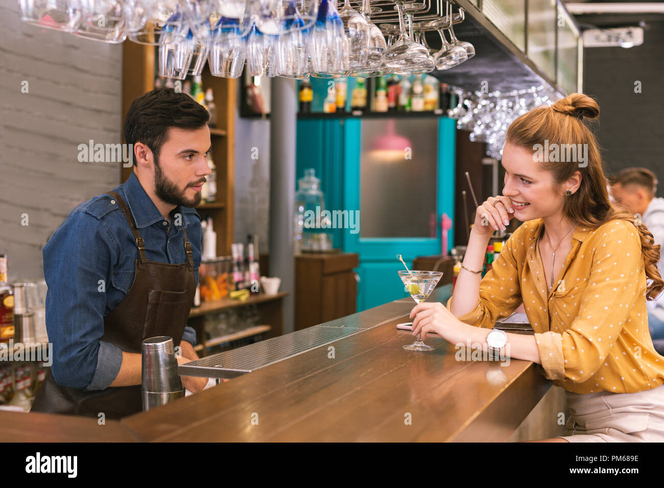 Pretty young girl smiling and flirting with the barman - Stock Image