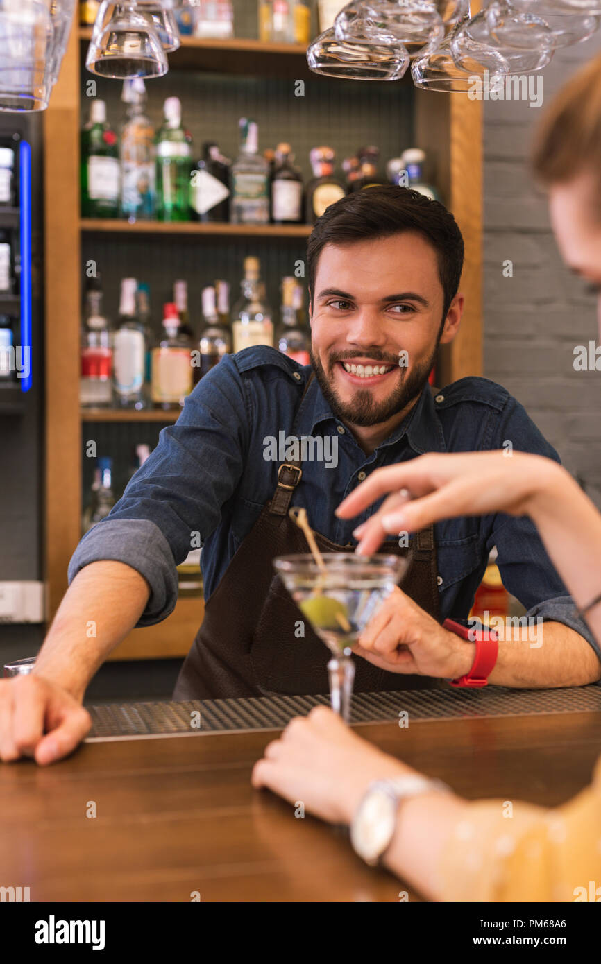 Handsome barman smiling and flirting with young visitor - Stock Image