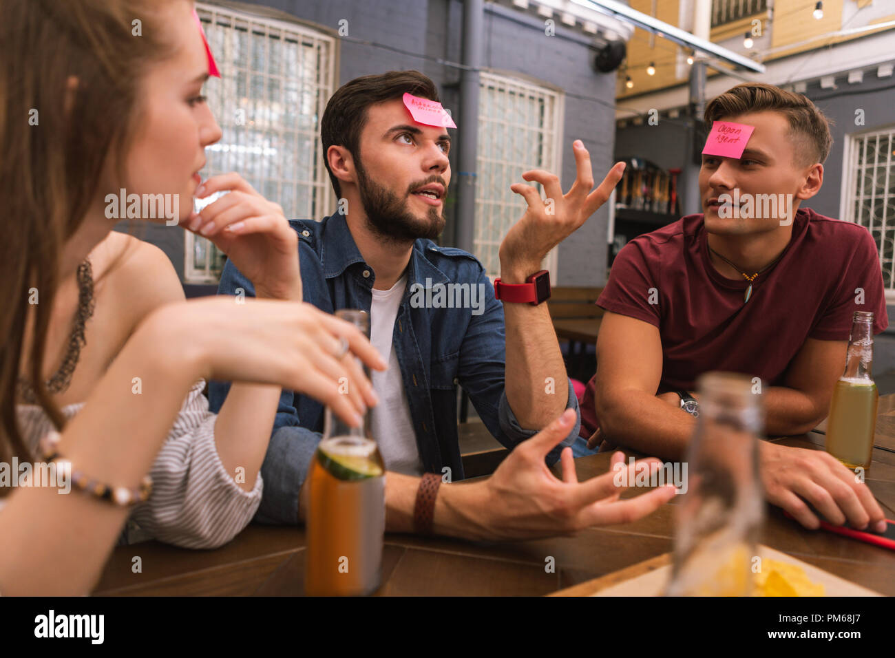 Thoughtful man using gestures and guessing the word in the game - Stock Image