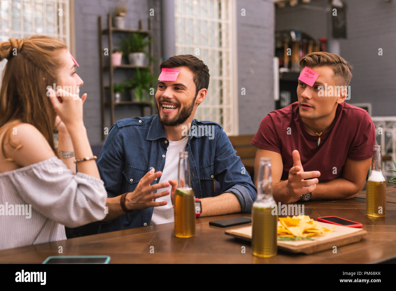 Excited friends having fun while playing games in the bar - Stock Image