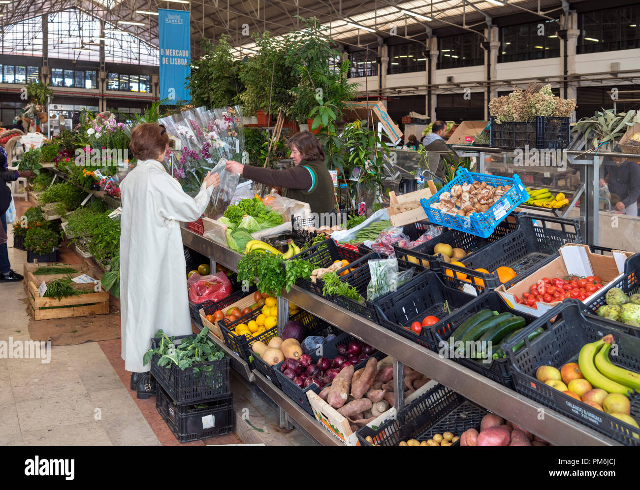 Woman buying produce at a fruit and vegetable market stall in the Mercado da Ribeira, Lisbon, Portugal - Stock Image