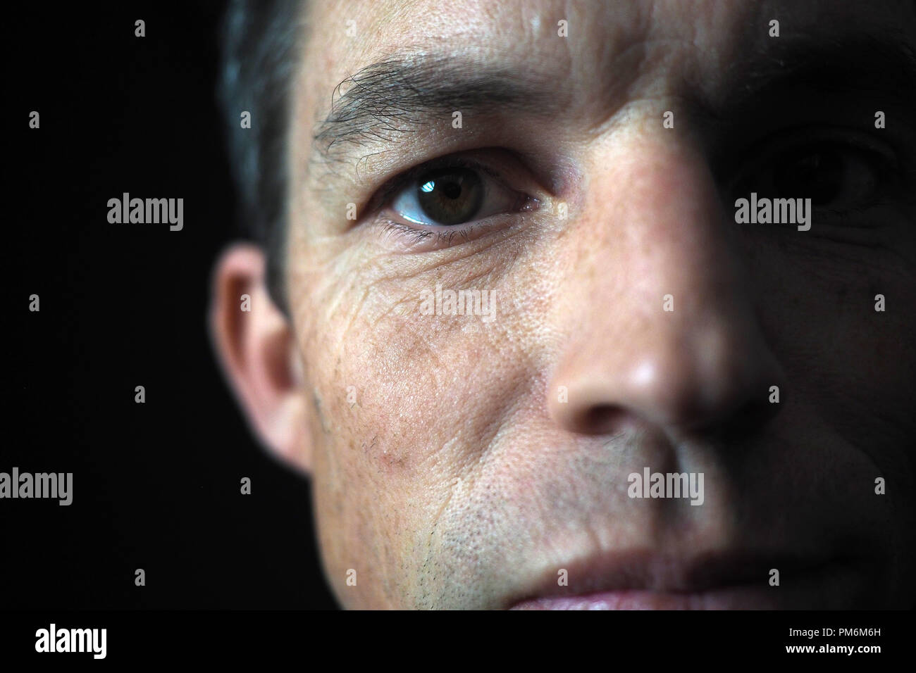 Portrait of man on black background, close up on eye Stock Photo