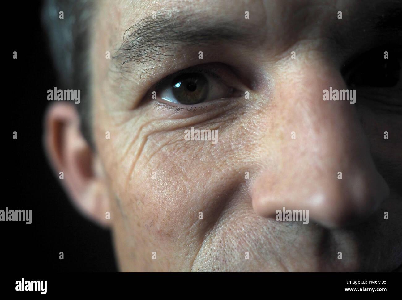 Portrait of man on black background, close up on eye Stock Photo