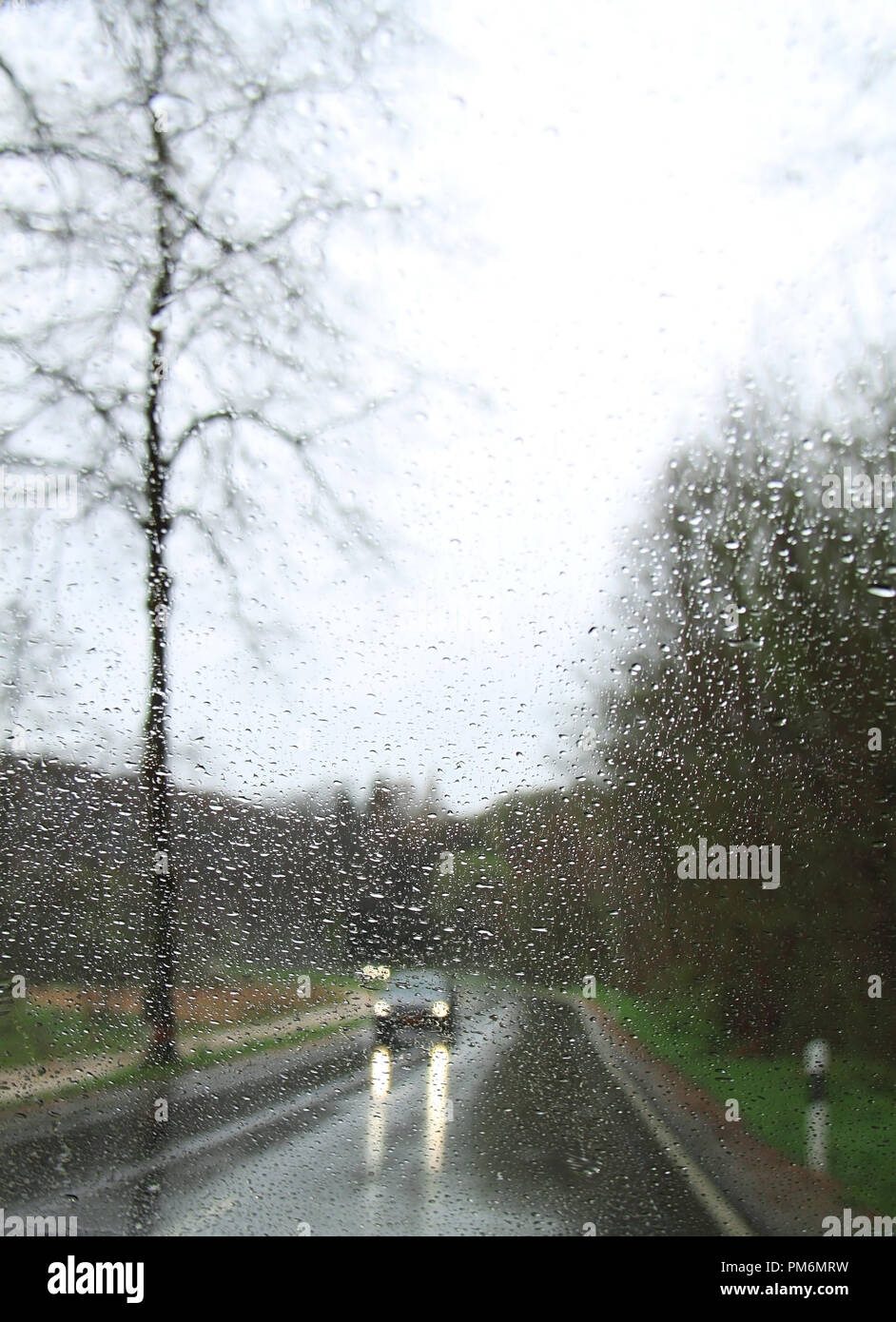 A car with headlights on viewed through a raindrop-covered windshield. Stock Photo