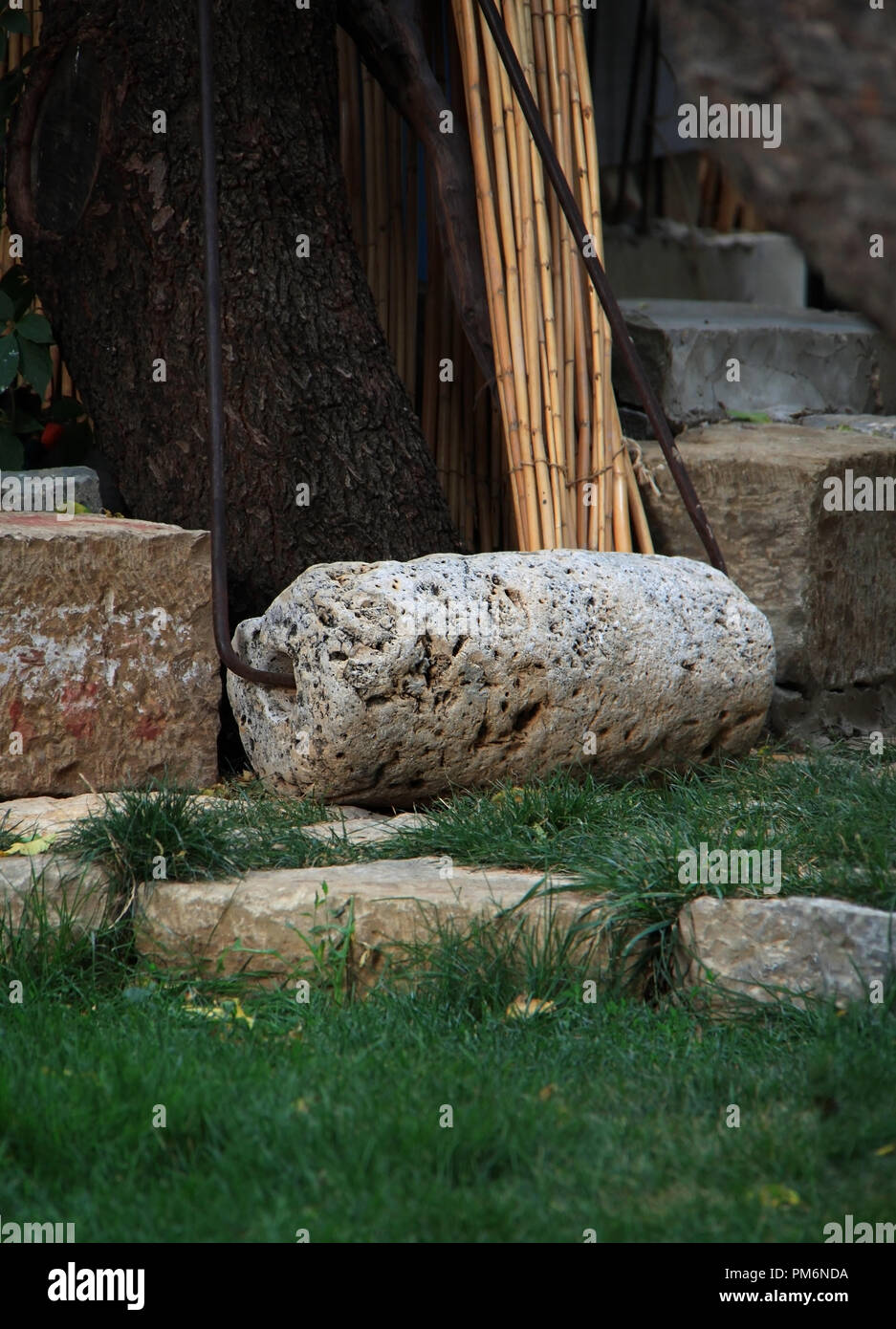 A rolling stone traditionally used construction in Lebanon, now obsolete and used only for decorating gardens. - Stock Image