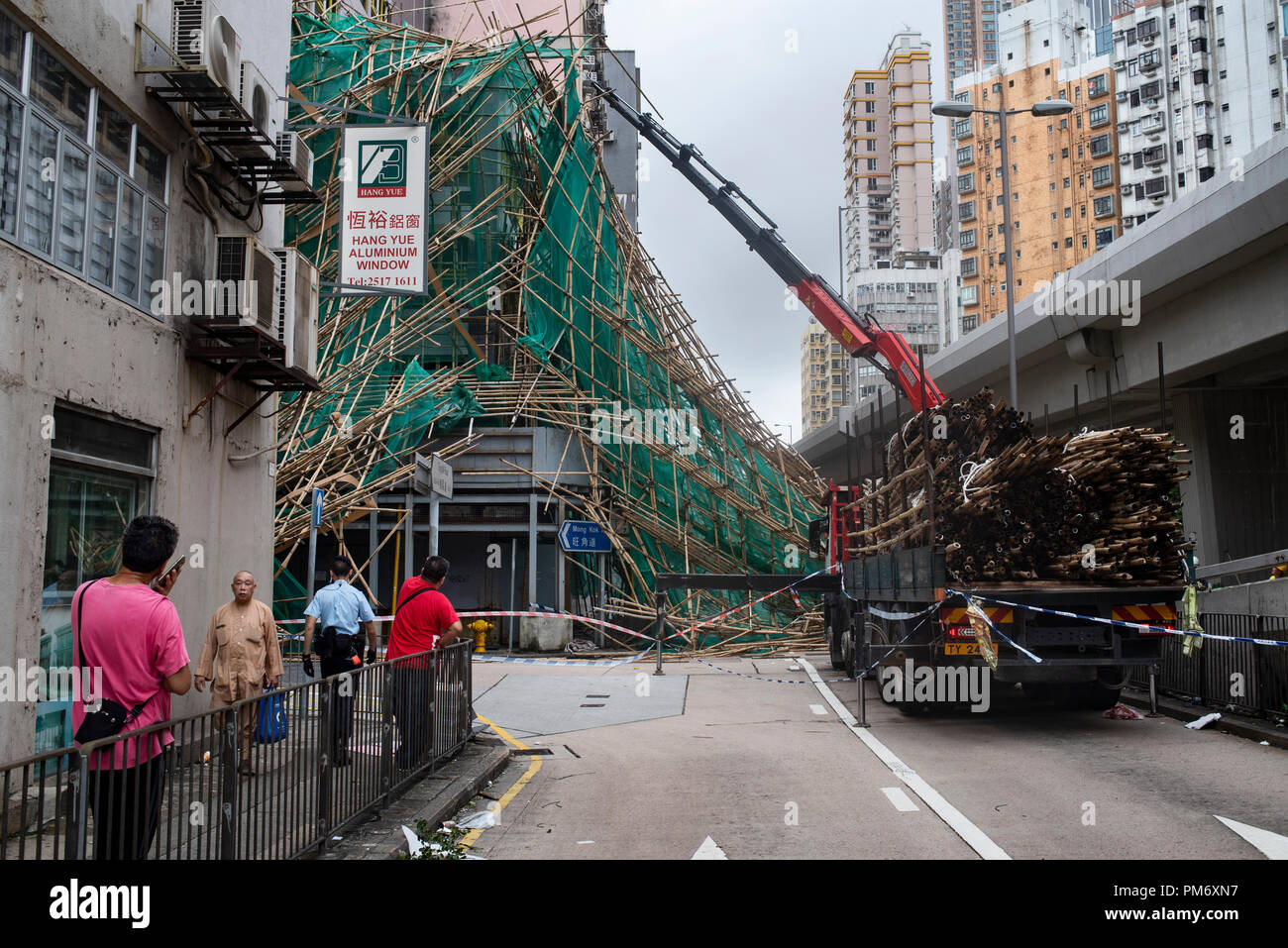 Workers remove bamboo scaffolding after it has collapse, fall and blocked the street. Super Typhoon Mangkhut aftermath is visible in most districts of Hong Kong. The super typhoon Mangkhut has passed next to Hong Kong on the 16th September causing large scale damages around the city, there are 432 people injured due to the storm with 2 still in critical condition. - Stock Image