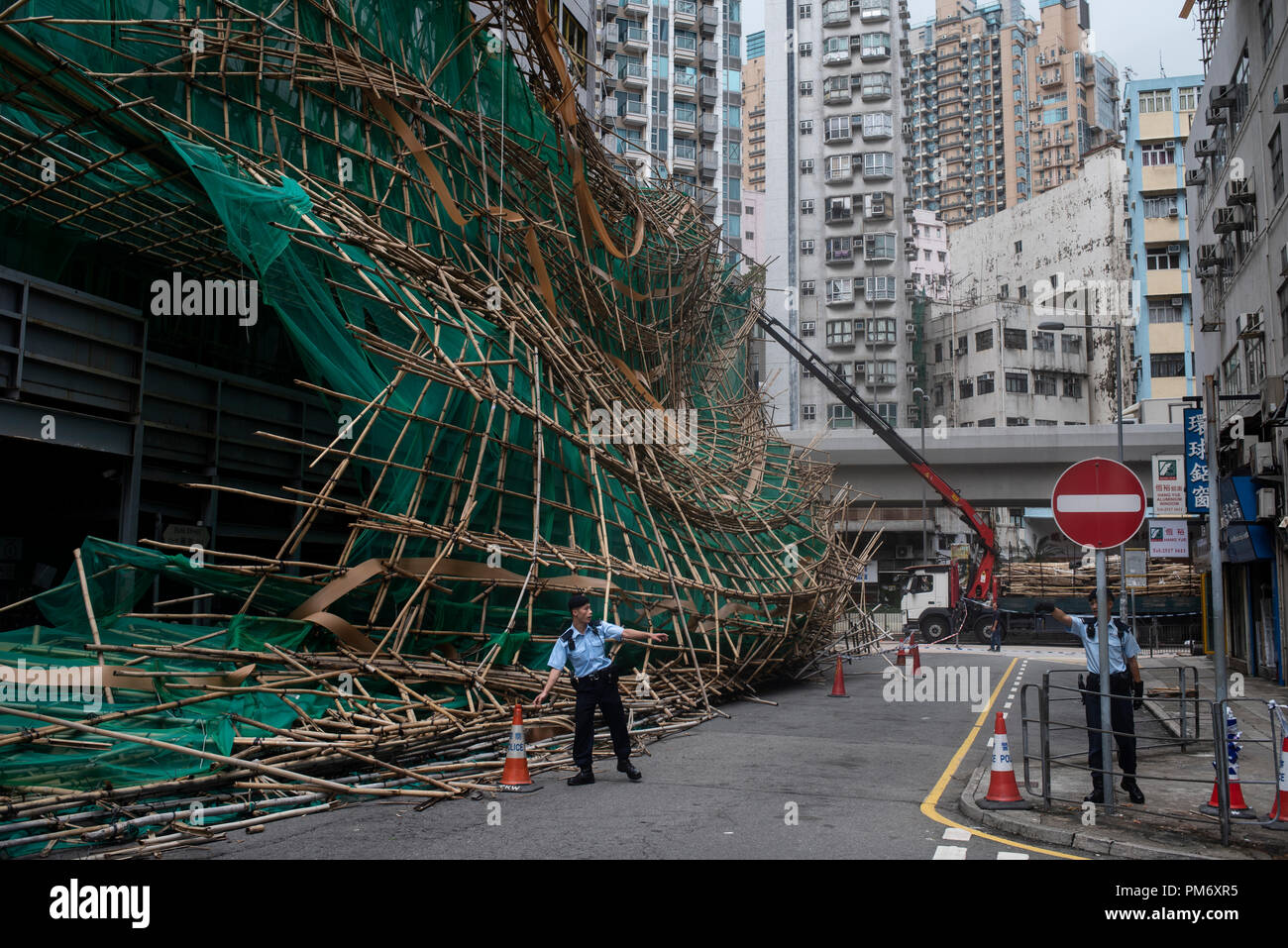 Police officers cut the street after bamboo scaffolding has collapsed and fall into the street. Super Typhoon Mangkhut aftermath is visible in most districts of Hong Kong. The super typhoon Mangkhut has passed next to Hong Kong on the 16th September causing large scale damages around the city, there are 432 people injured due to the storm with 2 still in critical condition. - Stock Image