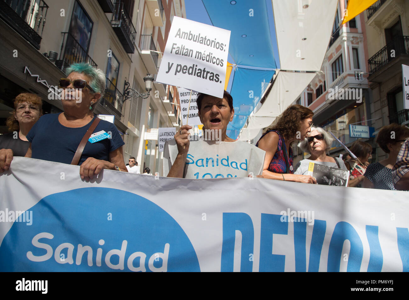 Two women seen behind a banner shouting slogans during the demonstration  in defense of Public Health and against cuts in the primary care of Public Health. - Stock Image