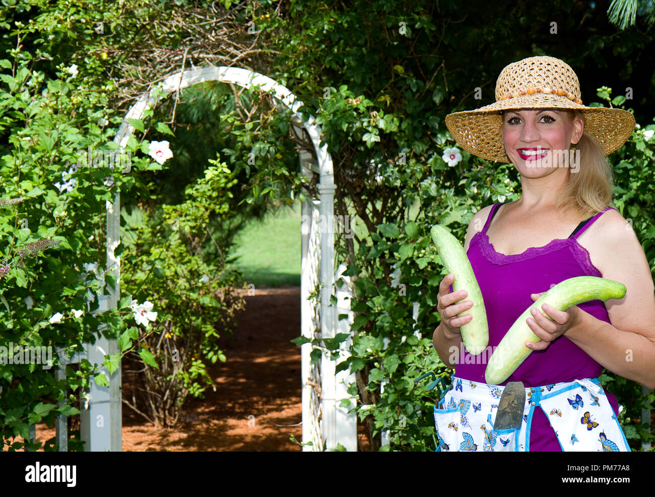 Woman working in her garden wearing sunhat and holding squash or flowers.  Lush green flowers and plants. Stock Photo