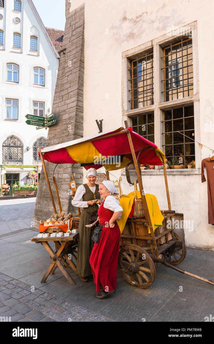 Tallinn medieval street, view of two young women in medieval dress supervising an almond stall in Vanaturu kael in Tallinn Old Town Estonia. - Stock Image