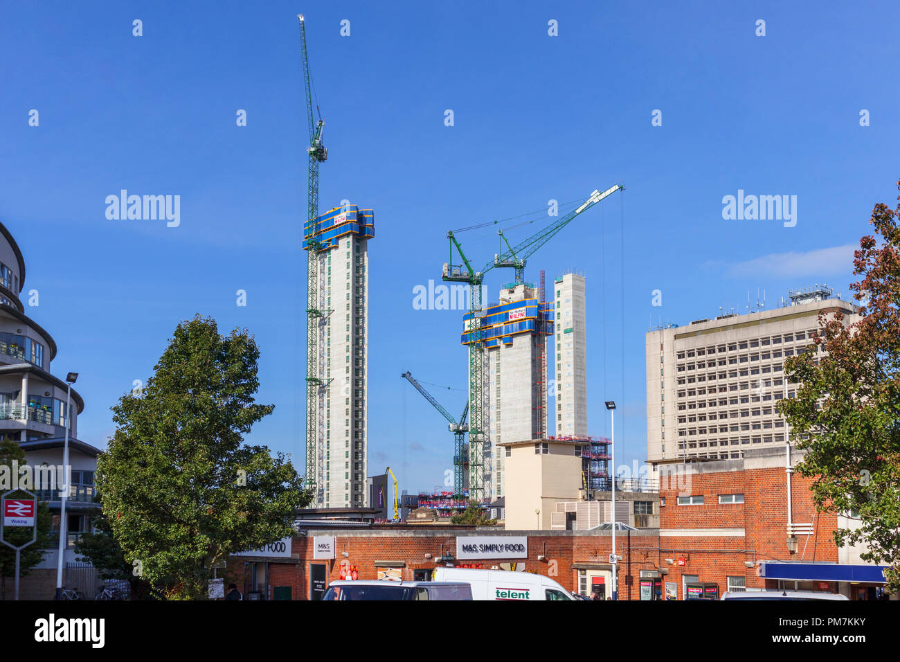 Cores and tower cranes of new mixed use Victoria Square development project under construction in Woking town centre viewed from the station on a sunny day - Stock Image