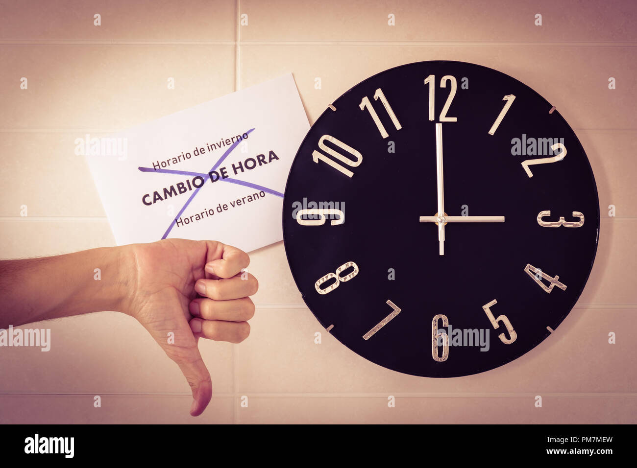 Big black clock on white wall. Time change. DST. Survey of the European Union. Gesture of disagreement . Thumb down of caucasian man. Spanish banner. - Stock Image