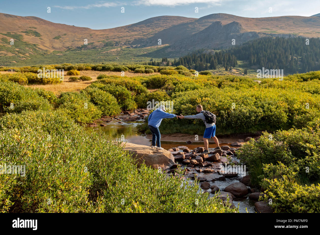 Georgetown, Colorado - An older woman gets help from a younger man in crossing a stream on the trail from Guanella Pass to 14,060-foot Mt. Bierstadt i - Stock Image